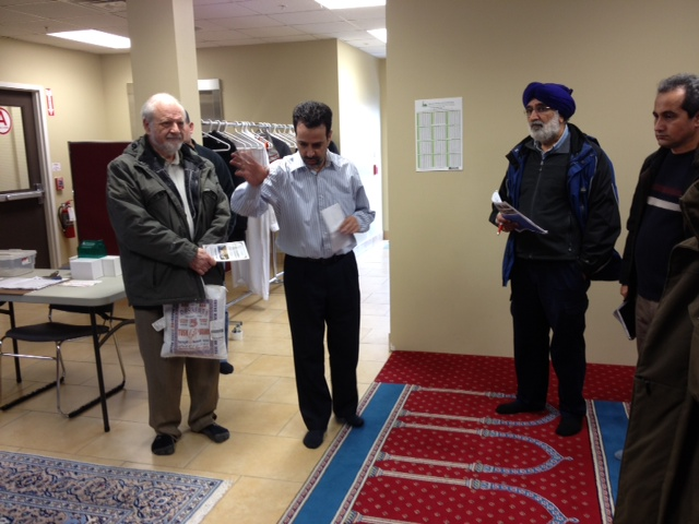 Congregational members involved in the energy efficient design of the Masjid Bilal mosque in Orleans explain its features to an interfaith group on a bus tour organized by Faith & the Common Good. Photo by Kathryn Norman.